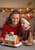 Happy mother and baby making christmas cookie house. Portrait of happy mother and baby making christmas cookie house in kitchen royalty free stock photos