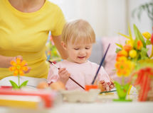 Happy mother and baby making Easter decorations Stock Photos