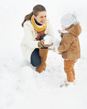 Happy mother and baby making snowman in winter park Royalty Free Stock Photos