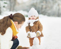 Happy mother and baby making snowman in winter park royalty free stock photography