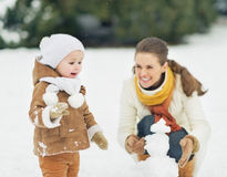 Happy mother and baby making snowman in winter park Stock Photography