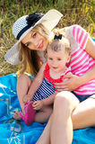 Happy mother with a baby in nature are resting Stock Images