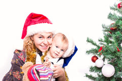 Happy mother and baby near Christmas tree Stock Photos