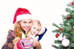 Happy mother and baby near Christmas tree Stock Photos