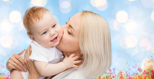 Happy mother with baby over natural background. People, family, motherhood and children concept - happy mother hugging adorable baby over blue lights and poppy Royalty Free Stock Photos