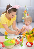 Happy mother and baby painting on Easter eggs Royalty Free Stock Photo