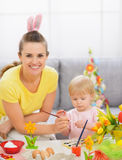 Happy mother and baby painting on Easter eggs Royalty Free Stock Photography