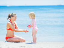 Happy mother and baby playing on beach Stock Photo