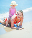 Happy mother and baby playing on beach Royalty Free Stock Photo