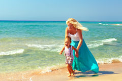Happy mother and baby playing on the beach Stock Photo