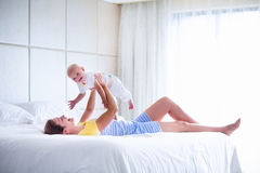 Happy mother and baby playing in bedroom Royalty Free Stock Image