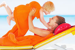 Happy mother and baby playing on chaise-longue. Happy young mother and baby girl playing on chaise-longue royalty free stock photo