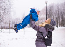 Happy mother and baby playing evergreen spruce in. Happy family enjoy snow and winter on holidays Royalty Free Stock Photography