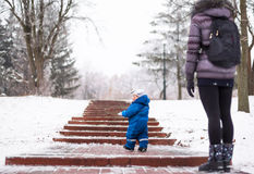 Happy mother and baby playing evergreen spruce in. Happy family enjoy snow and winter on holidays Stock Photo