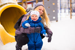 Happy mother and baby playing evergreen spruce in. Happy family enjoy snow and winter on holidays Royalty Free Stock Photo