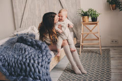 Happy mother and baby playing at home in bedroom. Cozy family lifestyle Stock Photography