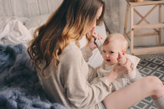 Happy mother and baby playing at home in bedroom. Cozy family lifestyle Stock Photos