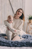 Happy mother and baby playing at home in bedroom. Cozy family lifestyle Royalty Free Stock Photography