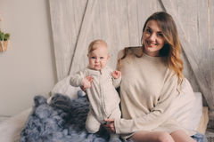 Happy mother and baby playing at home in bedroom. Cozy family lifestyle. In modern scandinavian interior royalty free stock images