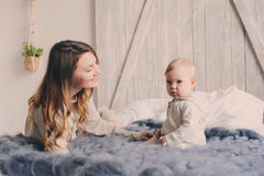 Happy mother and baby playing at home in bedroom. Cozy family lifestyle Stock Image