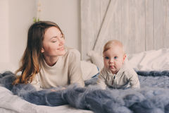 Happy mother and baby playing at home in bedroom. Cozy family lifestyle. In modern scandinavian interior royalty free stock photo
