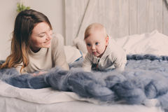 Happy mother and baby playing at home in bedroom. Cozy family lifestyle Stock Images