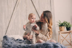 Happy mother and baby playing at home in bedroom. Cozy family lifestyle Royalty Free Stock Image