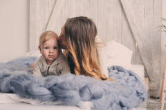 Happy mother and baby playing at home in bedroom. Cozy family lifestyle Stock Photo