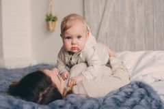 Happy mother and baby playing at home in bedroom. Cozy family lifestyle Royalty Free Stock Images