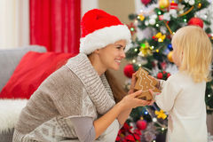 Happy mother and baby playing near Christmas tree Royalty Free Stock Photo