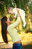 Happy mother and baby playing outdoors. Royalty Free Stock Photo