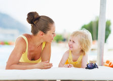 Happy mother and baby playing at poolside Royalty Free Stock Photos