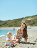 Happy mother and baby playing with sand on beach. Happy mother and baby girl playing with sand on beach Royalty Free Stock Images