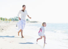 Happy mother and baby playing on sea coast Stock Photo