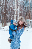 Happy mother and baby playing on snow Stock Photography