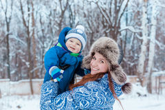 Happy mother and baby playing on snow Royalty Free Stock Photo