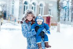 Happy mother and baby playing on snow Stock Image
