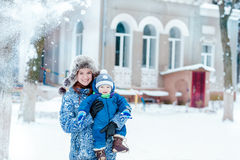 Happy mother and baby playing on snow Stock Photos