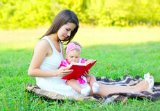 Happy mother with baby reading book sitting on grass in summer Stock Photo