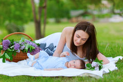 Happy  mother and baby resting in summer park Royalty Free Stock Images