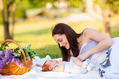 Happy  mother and baby resting in summer park Stock Image