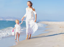 Happy mother and baby running along sea coast Stock Image