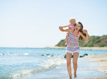 Happy mother with baby running along sea shore Royalty Free Stock Images