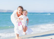 Happy mother and baby on sea shore having fun Stock Photo