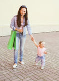 Happy mother and baby with shopping bags walking Stock Image