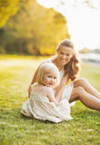 Happy mother and baby sitting on meadow in park Stock Photography
