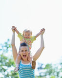 Happy mother with baby sitting on shoulders Stock Photo