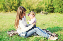 Happy mother and baby sitting together on grass Stock Photo