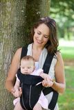 Happy mother with baby in sling Royalty Free Stock Photos