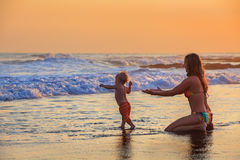 Happy mother, baby son has fun in sea beach surf. Family swimming fun in sea beach surf Happy mother, baby son first step - toddler run to ocean wave on sunset Royalty Free Stock Photography